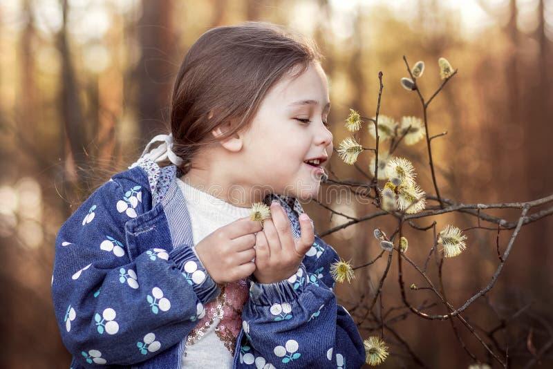La bambina sulla natura esamina le piante immagine stock