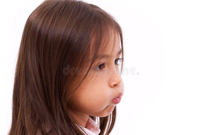 La bambina sveglia adorabile increspa la sua bocca fotografia stock libera da diritti