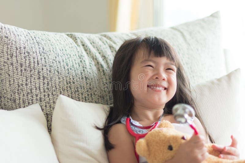 La bambina sveglia asiatica è sorridente e giocante al dottore con lo stetho fotografie stock