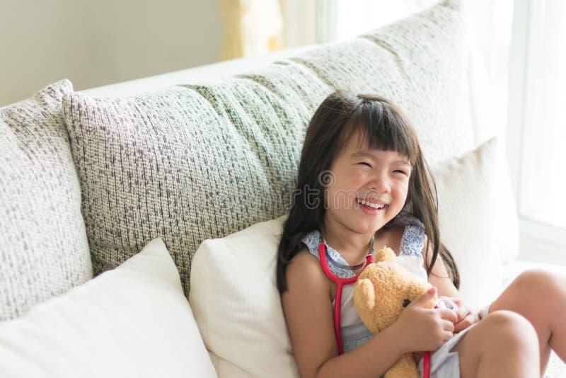La bambina sveglia asiatica è sorridente e giocante al dottore con lo stetho fotografia stock