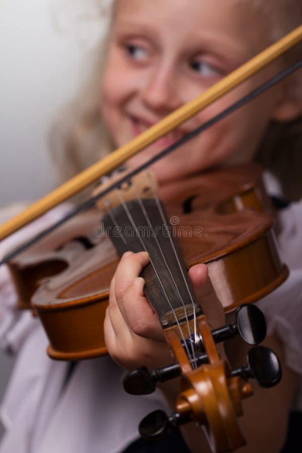 La bambina sveglia in blusa luminosa gioca il primo piano del violino su un fondo grigio fotografia stock