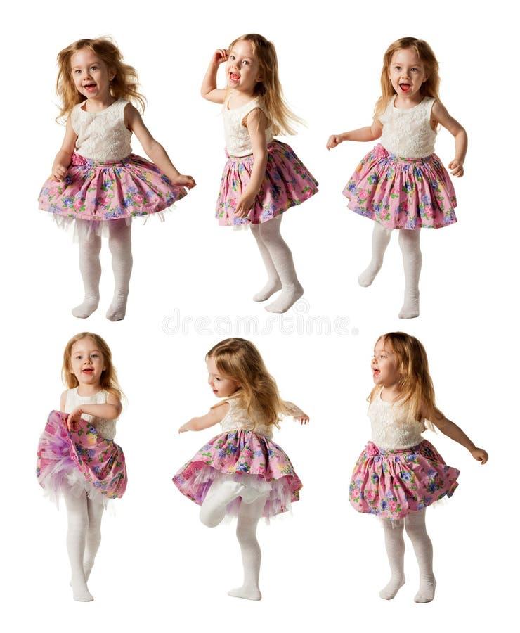 La bambina sveglia canta la canzone e sta ballando ha isolato sul BAC bianco immagini stock
