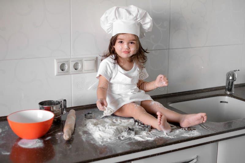 La bambina sveglia in cappello del cuoco unico e del grembiule sta impastando la pasta e sta sorridendo mentre coceva immagine stock