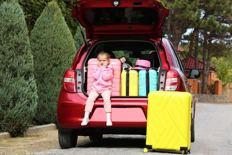 La bambina sveglia che si siede nel tronco di automobile ha caricato con le valigie fotografia stock libera da diritti