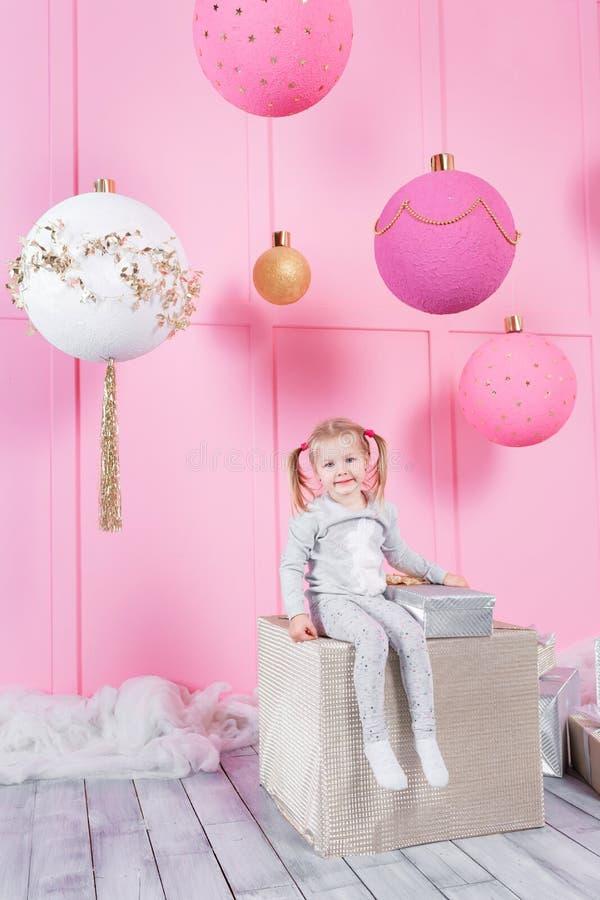 La bambina sveglia che si siede in una sedia ed apre una scatola con un presente per l 39 albero di - Finestra che si apre ...