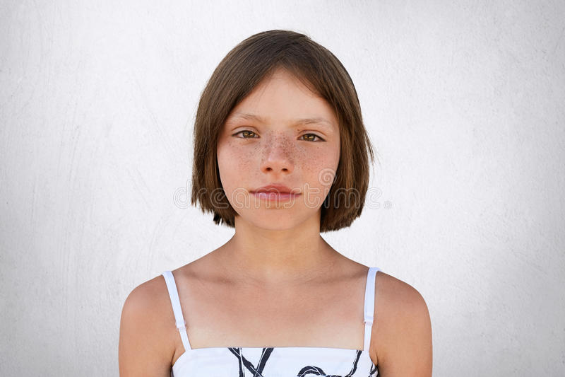 La bambina sveglia con breve buio ha ballonzolato capelli, marrone largamente che splendono gli occhi, labbra sottili e sguardo b fotografia stock