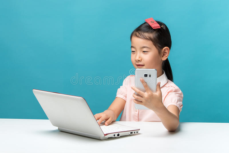 La bambina sveglia dell'Asia sta sedendosi alla tavola con il suo computer portatile bianco e smartphones, isolati sopra il blu immagine stock libera da diritti