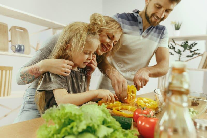 La bambina sveglia ed i suoi bei genitori stanno tagliando le verdure in cucina a casa immagine stock libera da diritti