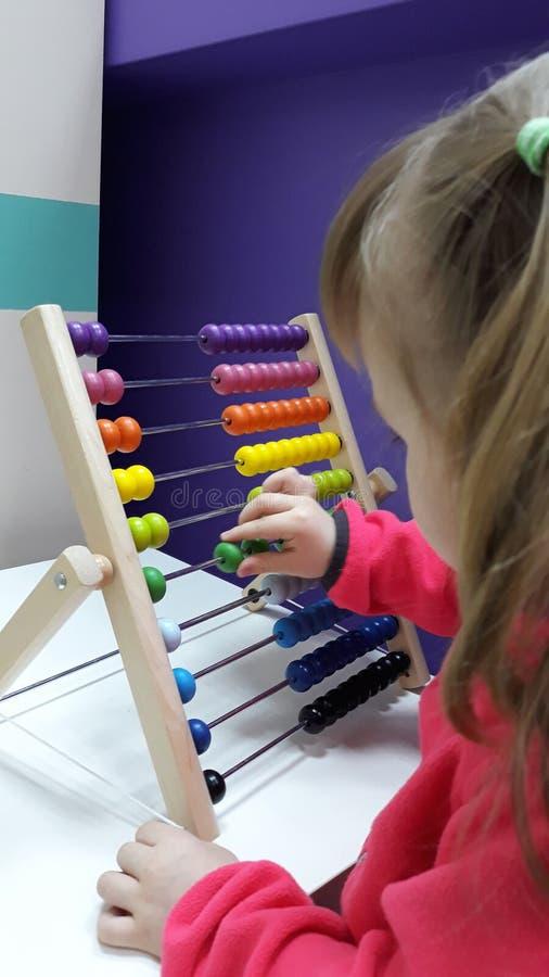 La bambina sveglia gioca l'abaco di legno Neonata che conta con la guida di un abbaco Bambino astuto che impara contare fotografia stock libera da diritti