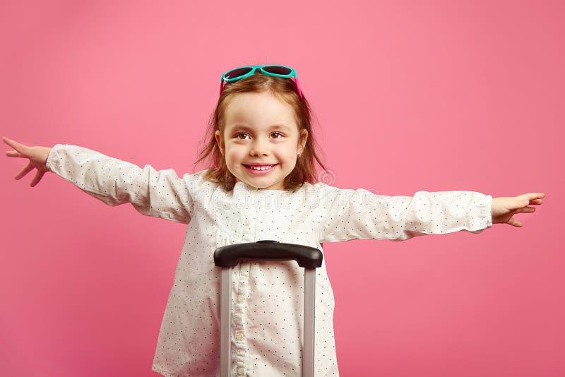 La bambina sveglia ha esteso le armi, descrive un aereo, sorridente felicemente, supporti vicino alla valigia sul rosa fotografia stock libera da diritti