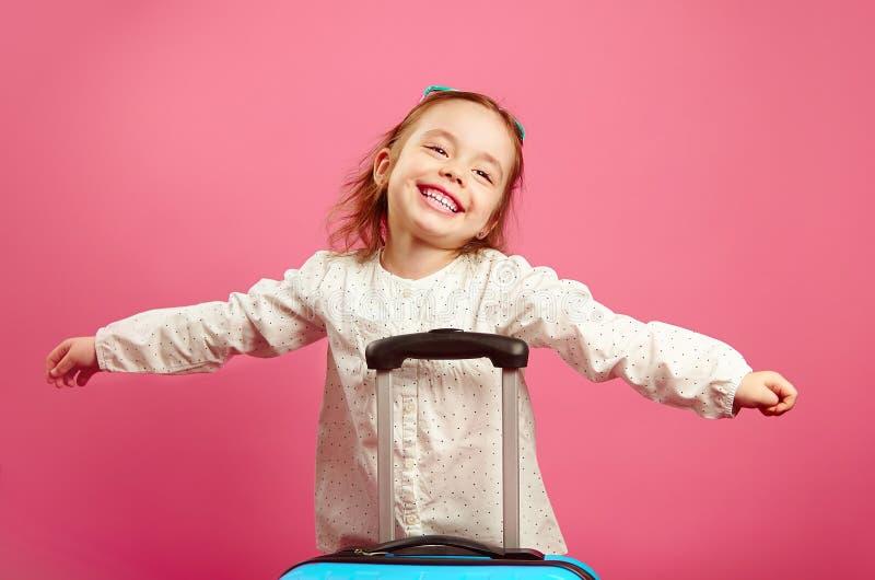 La bambina sveglia ha esteso le armi, descrive un aereo, sorridente felicemente, supporti vicino alla valigia sul rosa fotografie stock libere da diritti