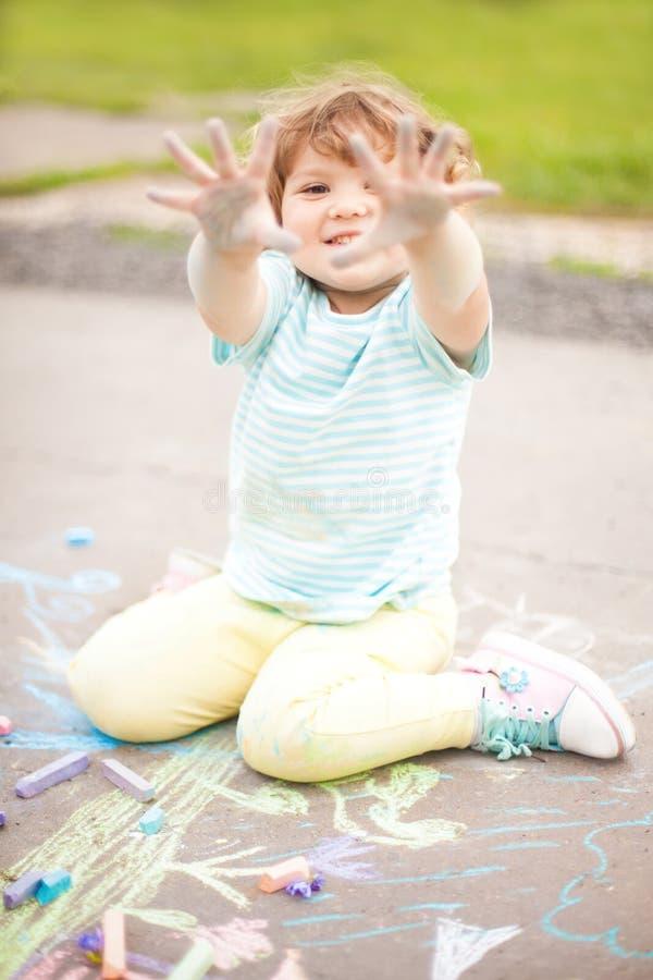 La bambina sveglia le mostra le mani macchiate colore fotografia stock libera da diritti