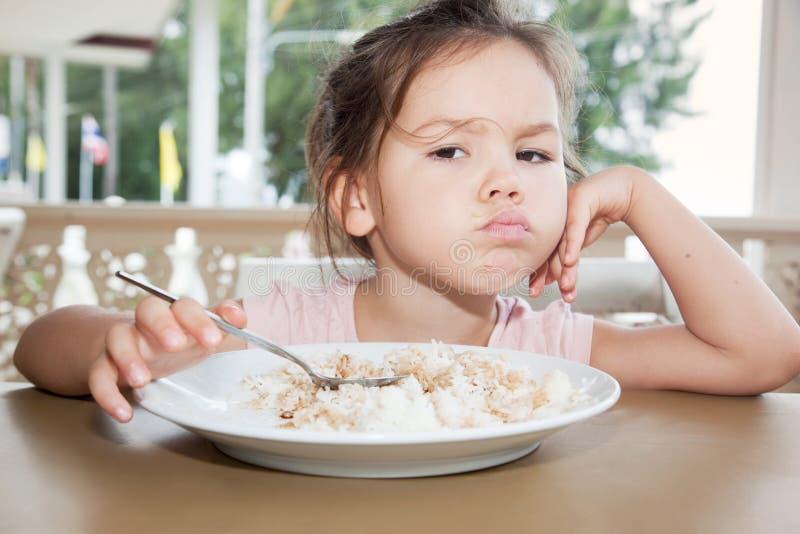 La bambina sveglia mangia il riso in un caffè dell'estate immagine stock libera da diritti