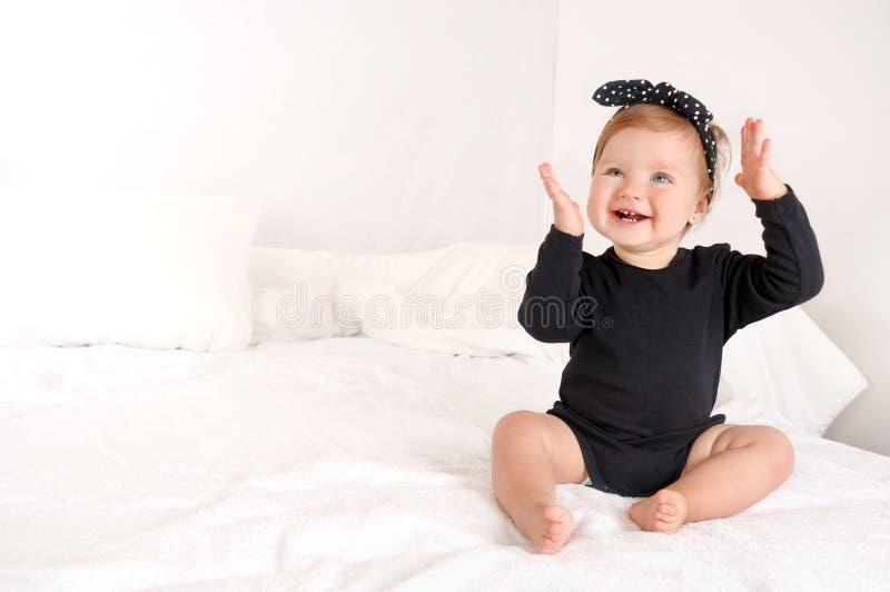 La bambina sveglia si siede sul letto a casa fotografia stock libera da diritti