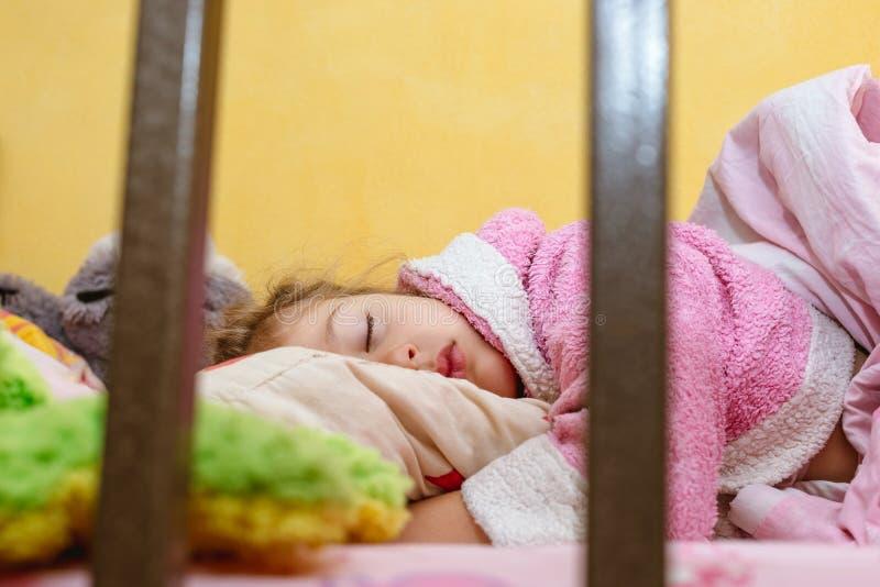 La bambina sveglia sta dormendo sul secondo piano di un letto di cuccetta fotografia stock