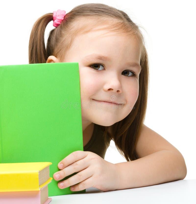 La bambina sveglia sta nascondendosi dietro un libro immagini stock