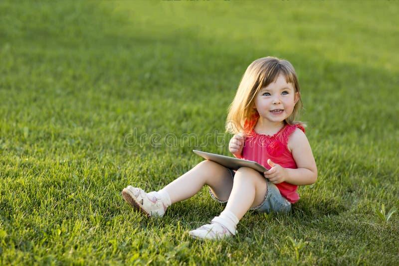 La bambina sveglia sta sedendosi con una compressa sull'erba nel parco Ritratto impressionabile Formazione iniziale immagini stock