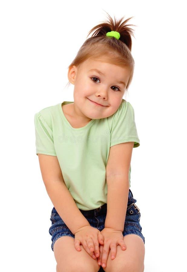 La bambina sveglia sta sedendosi sul pavimento e sul sorriso immagine stock libera da diritti