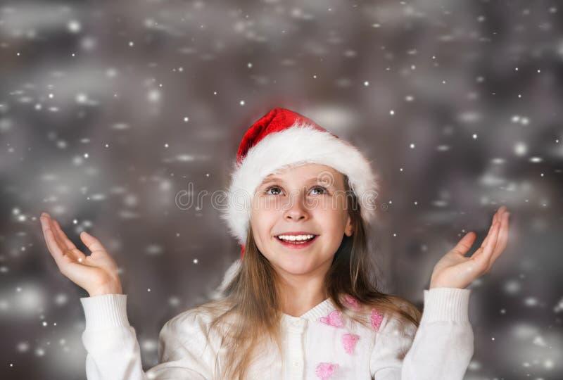 La bambina sveglia in un cappello di Natale gode della neve di caduta immagini stock libere da diritti