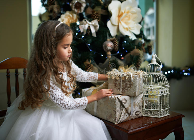La bambina sveglia in vestito bianco esamina i regali fotografie stock