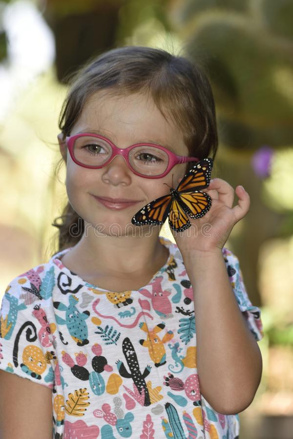 La bambina tiene in sue mani una farfalla di monarca fotografia stock libera da diritti