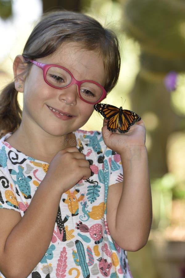 La bambina tiene in sue mani una farfalla di monarca immagine stock libera da diritti