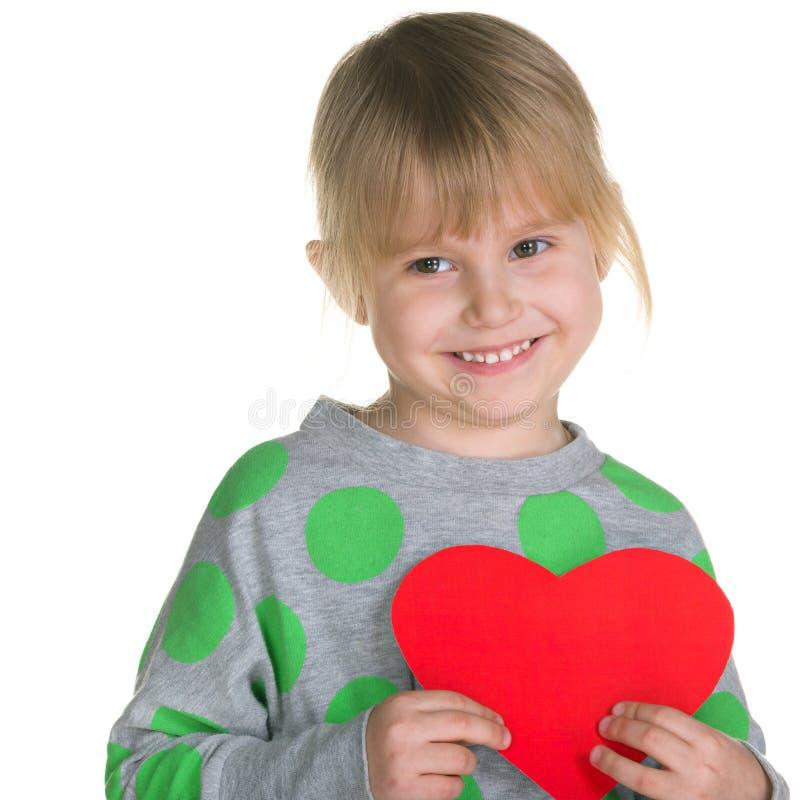 La bambina tiene un cuore rosso fotografia stock