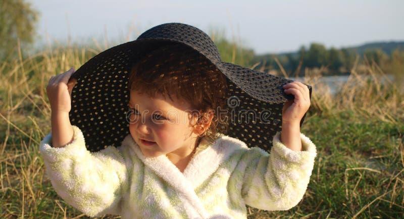 La bambina in un abito bianco di Terry prova sopra un cappello nero del sole fotografia stock libera da diritti