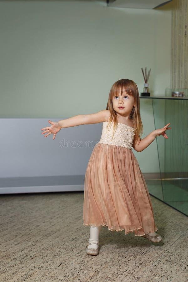 La bambina in un bello vestito gioca a casa immagini stock