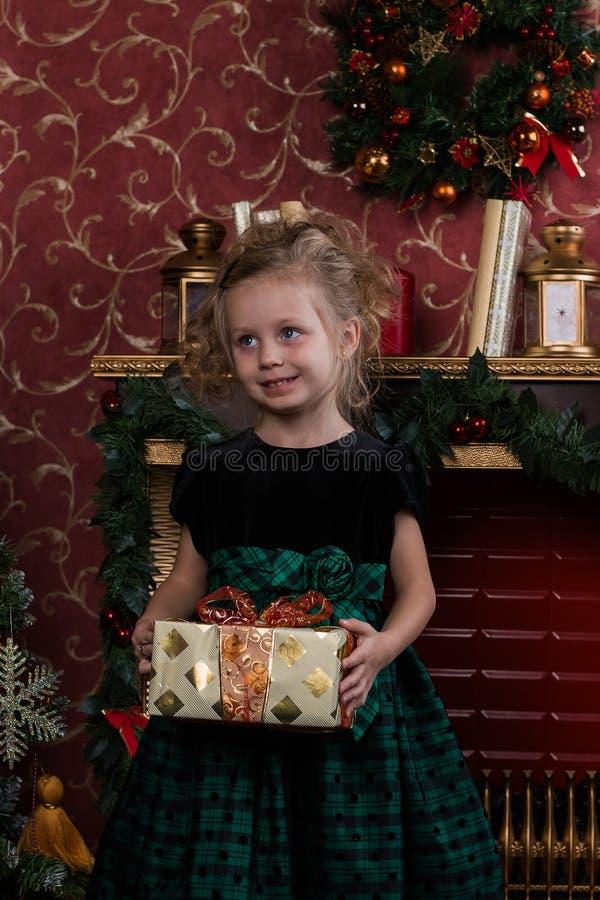 La bambina in un giorno dei nuovi anni è intorno al camino sta tenendo un regalo Stanza decorata con le decorazioni di Natale immagini stock libere da diritti
