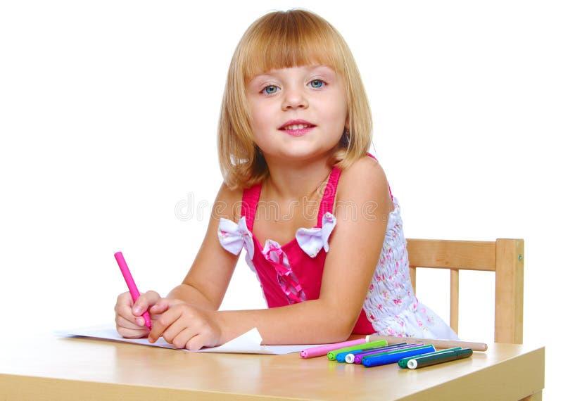 La bambina in un vestito rosso disegna fotografia stock