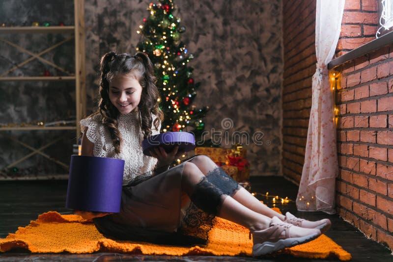 La bambina in un vestito si siede sul pavimento a casa vicino all'albero di Natale e tiene una scatola con i regali fotografia stock libera da diritti
