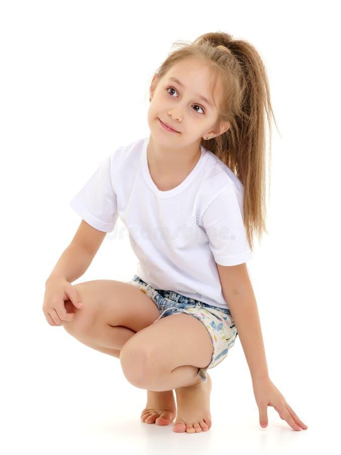 La bambina in una maglietta bianca pura per la pubblicità e mette fotografie stock