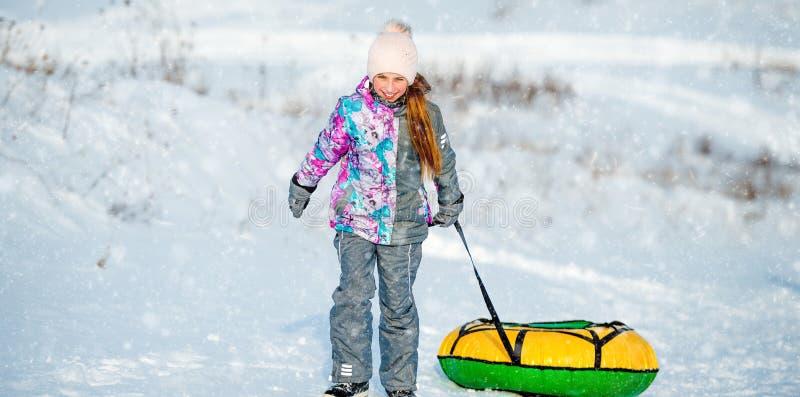 La bambina va per lo scorrevole dell'inverno immagini stock