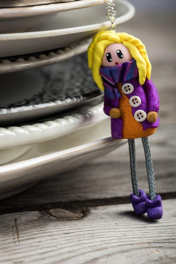 La bambola abbastanza bionda si è vestita in porpora ed in arancio immagine stock