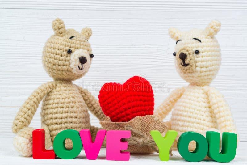 La bambola dolce dell'orsacchiotto delle coppie nell'amore con il testo di amore ed il rosso tricottano fotografia stock libera da diritti