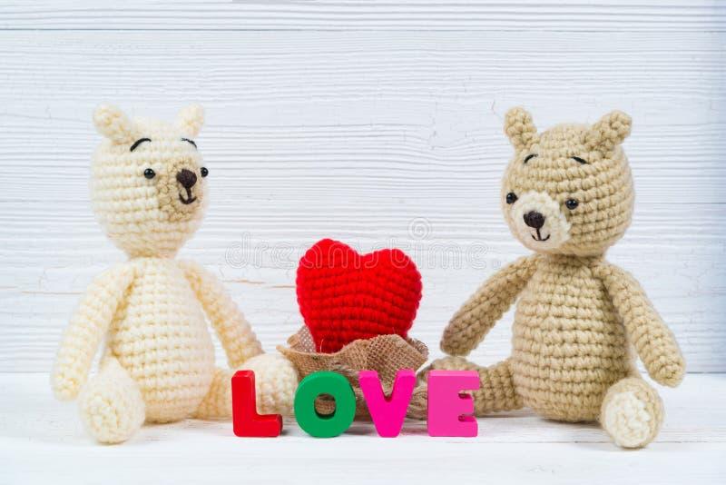 La bambola dolce dell'orsacchiotto delle coppie nell'amore con il testo di amore ed il rosso tricottano immagini stock