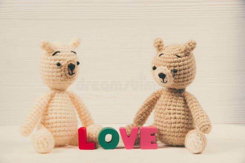 La bambola dolce dell'orsacchiotto delle coppie nell'amore con il testo di amore ed il rosso tricottano fotografia stock