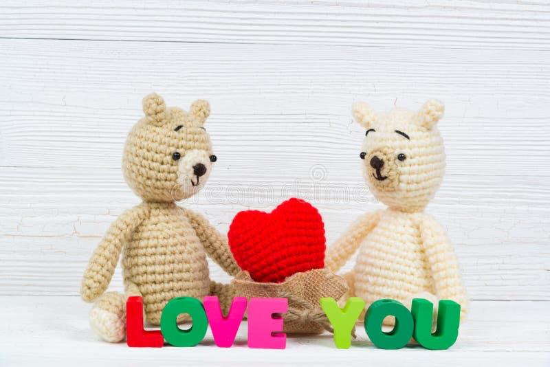 La bambola dolce dell'orsacchiotto delle coppie nell'amore con il testo di amore ed il rosso tricottano fotografie stock libere da diritti