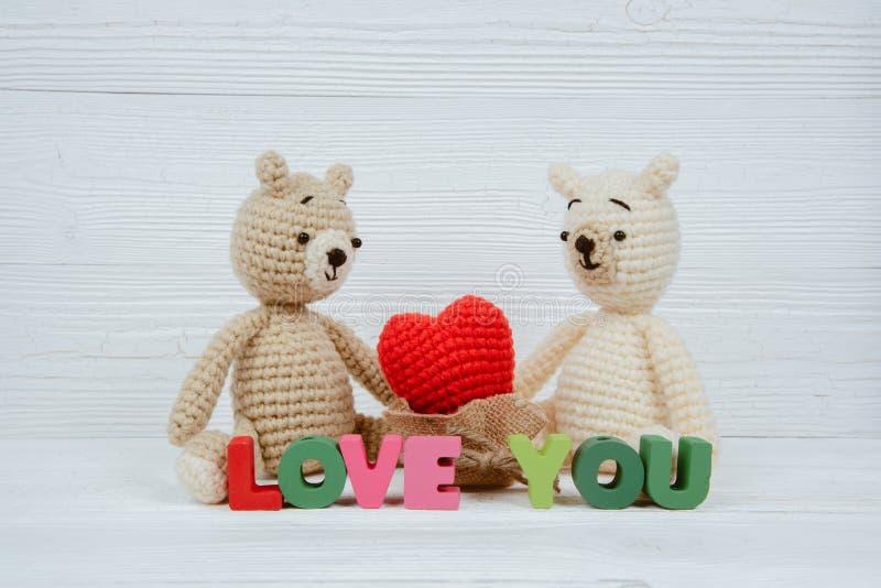 La bambola dolce dell'orsacchiotto delle coppie nell'amore con il testo di amore ed il rosso tricottano immagine stock libera da diritti