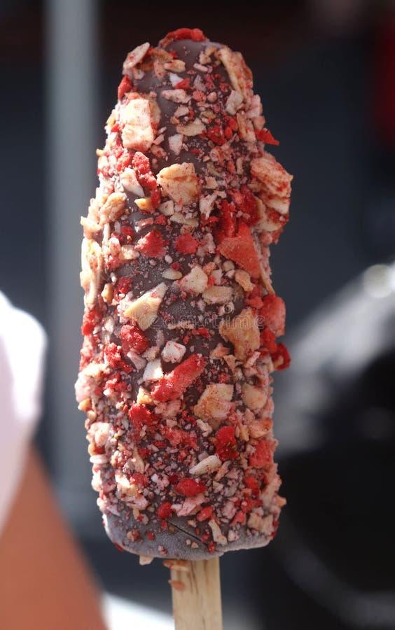 La banana congelata coperta di cioccolato con i dadi e la caramella spruzza immagini stock libere da diritti