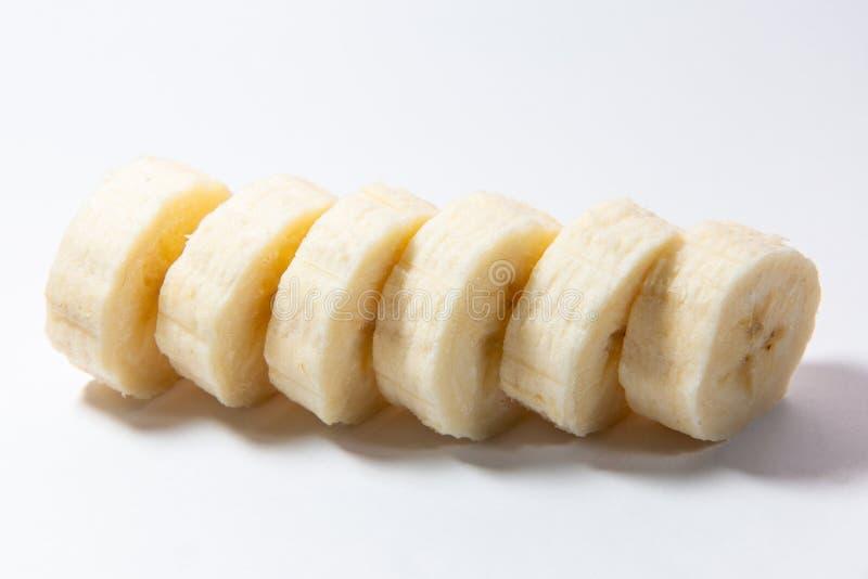 La banana sbucciata affettata si trova su un fondo bianco fotografia stock libera da diritti