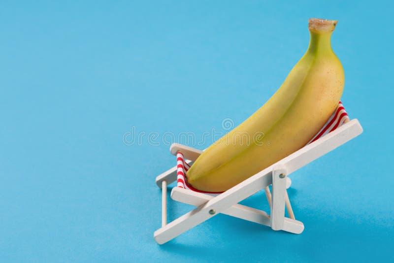 La banana si trova in una sedia di salotto, su un fondo blu, sul concetto della vacanza e sul rilassamento immagini stock