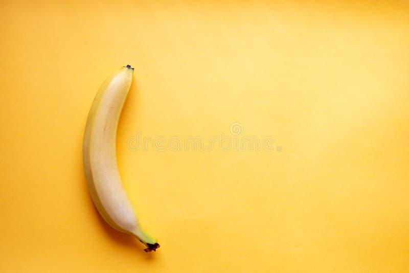 La banane se trouve verticalement sur un fond jaune Disposition plat photographie stock