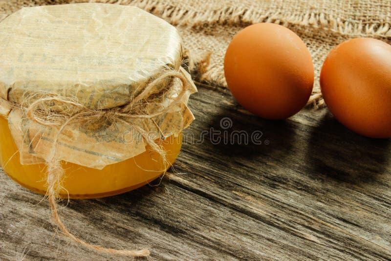 La Banca con miele con le uova crude su un fondo di legno grigio Vista laterale agricoltura immagine stock libera da diritti