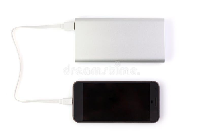 La banca di alimentazione carica lo smartphone su fondo bianco Batteria esterna universale per gadget Banca di alimentazione per  immagini stock libere da diritti