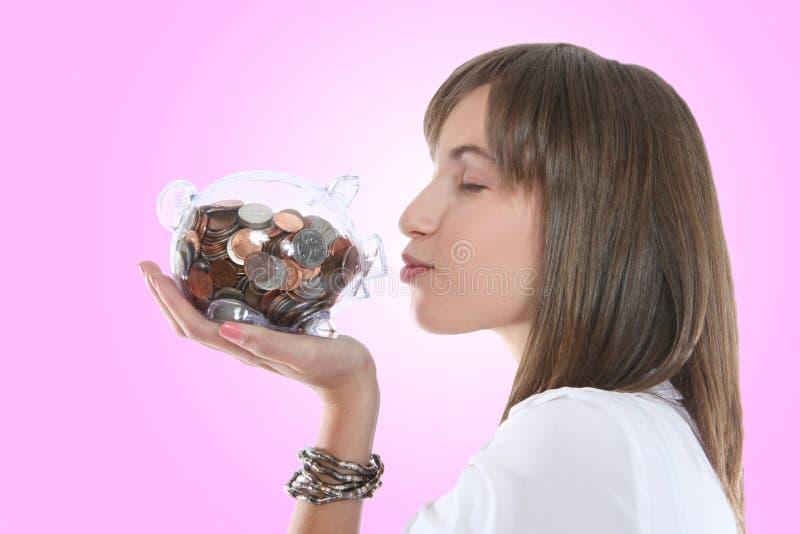 La Banca Piggy baciante della donna graziosa fotografie stock