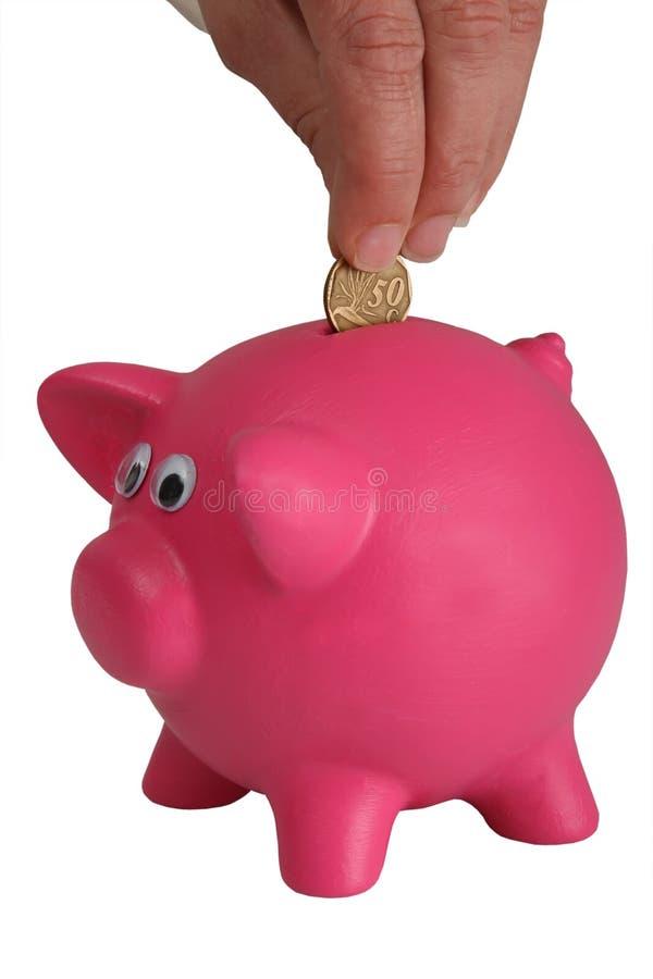 La Banca Piggy e mano con la moneta immagine stock