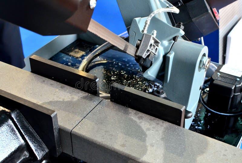 La banda automática del CNC vio la barra de acero de herramienta de corte al lado de la alimentación automática imagen de archivo
