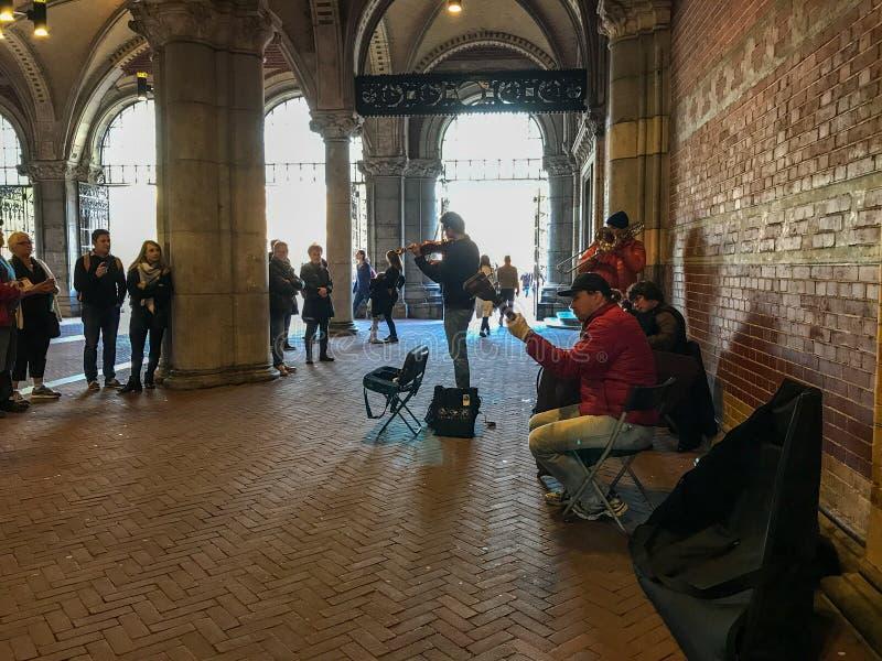 La banda de Busking dibuja a la audiencia debajo de los arcos de Rijksmuseum, Amsterdam foto de archivo libre de regalías